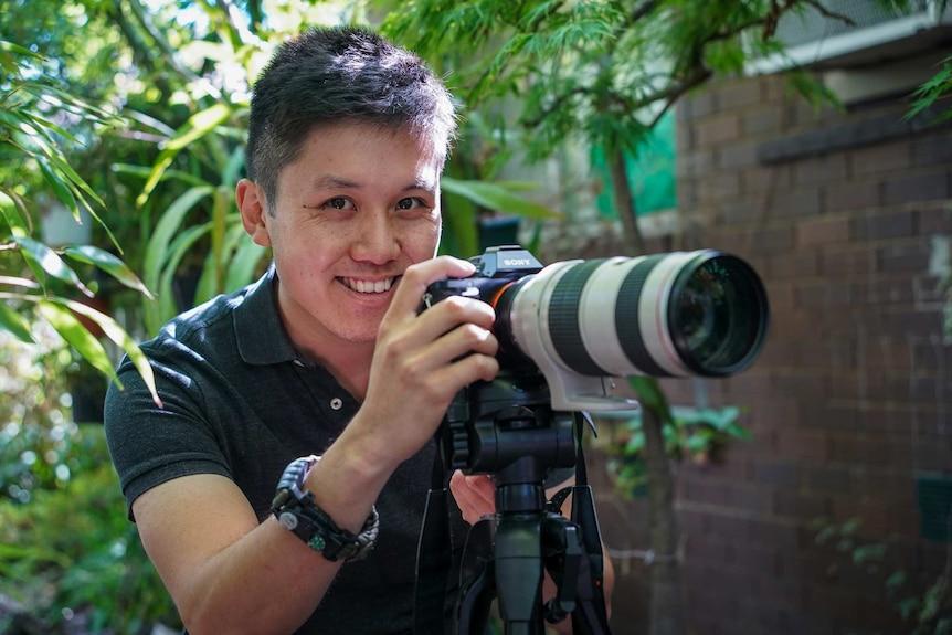 A man holds a camera.