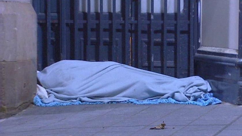 a homeless person under a blanket.