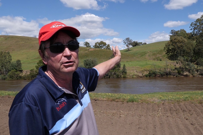 A farmer wearing sunglasses and a red hat gestures at some hills behind him.