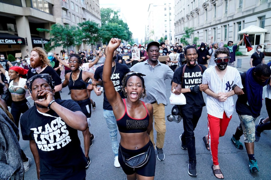 A crowd of people wearing black shirts and pants walks down a street shouting.