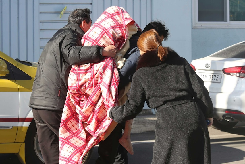An injured person covered in a red and white blanket is carried away from a hospital fire by three people.