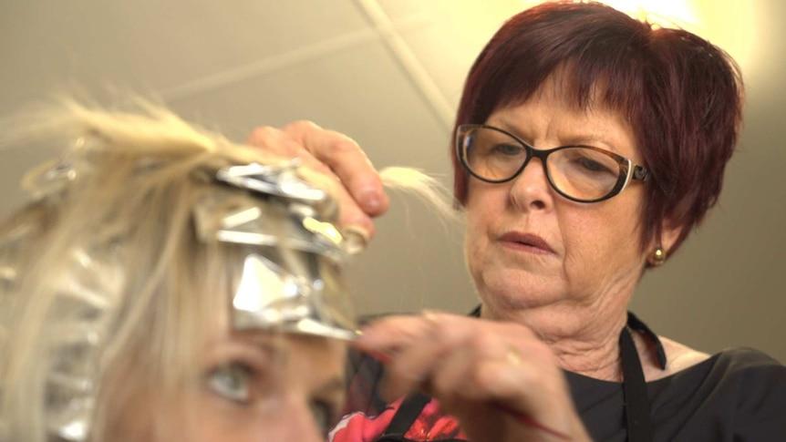 Hairdresser gives client foils