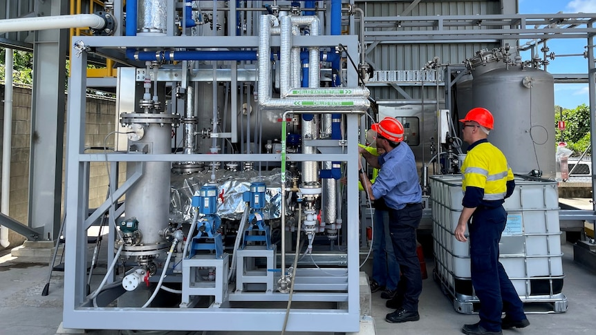 Two men wearing orange hard hats examine equipment and pipes of a biorefinery plant.