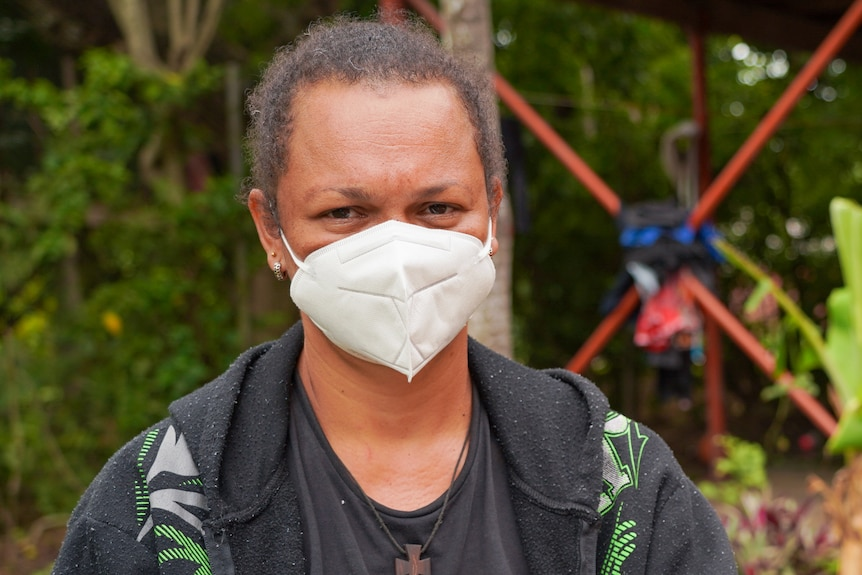 A Papua New Guinean woman in a white face mask