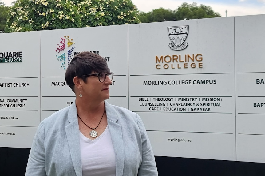 Woman wearing light blue jacket and white shirt standing outside Morling College campus sign.