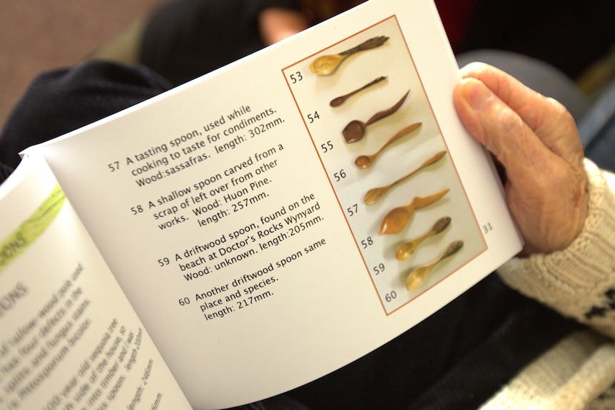 An open book, showing photographs of wooden spoons alongside descriptions of them, held by an old hand.