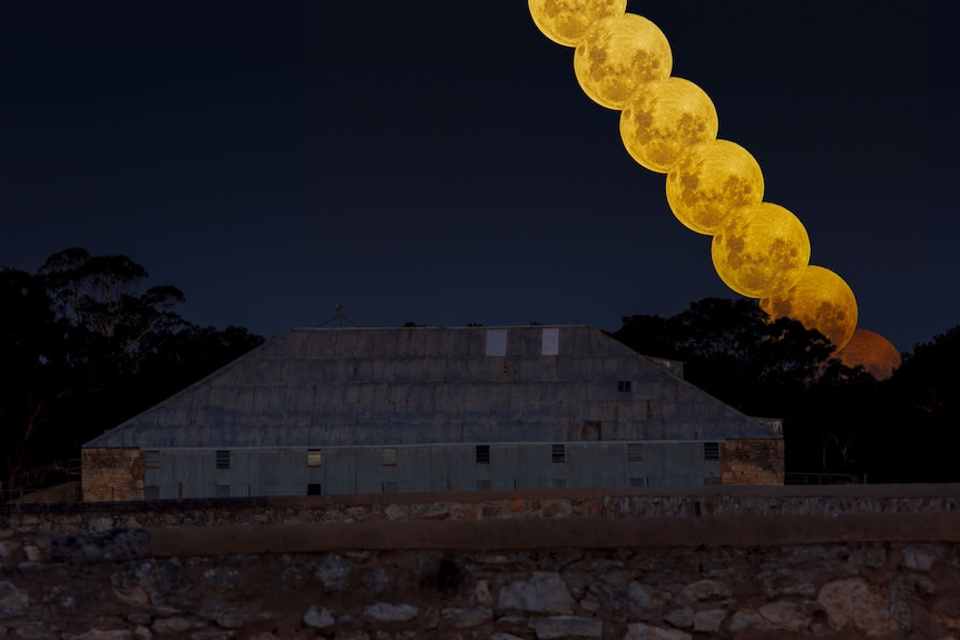 A line of yellow moons appear over a stone building under a blue night sky.