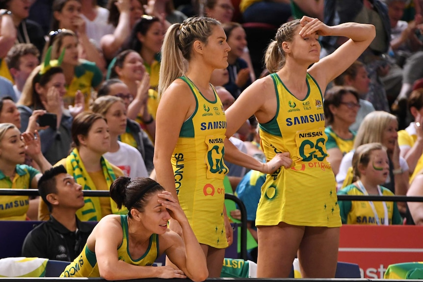 A group of netball teammates grimace as they watch time run out in a loss.