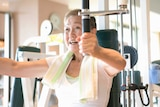 An older woman using a weight machine at the gym.