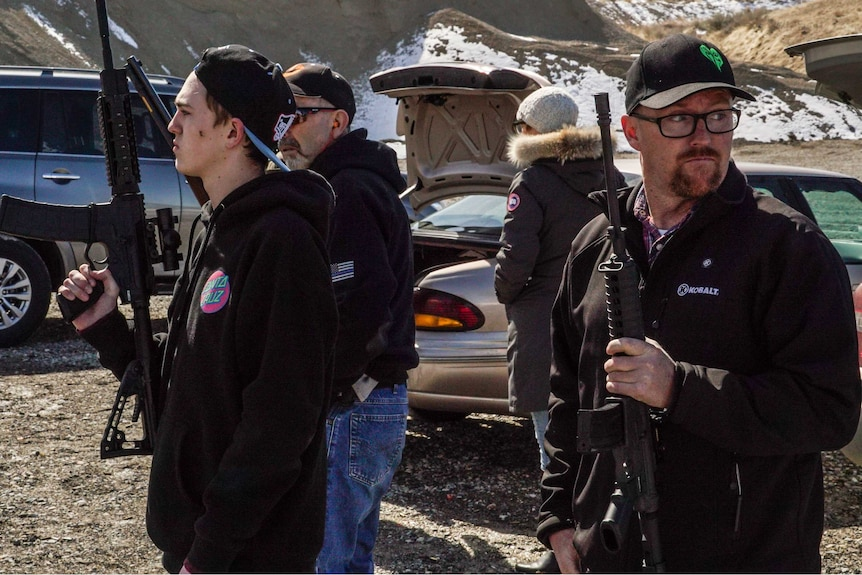 Two men wearing caps with AR-15 rifles in a snowy valley