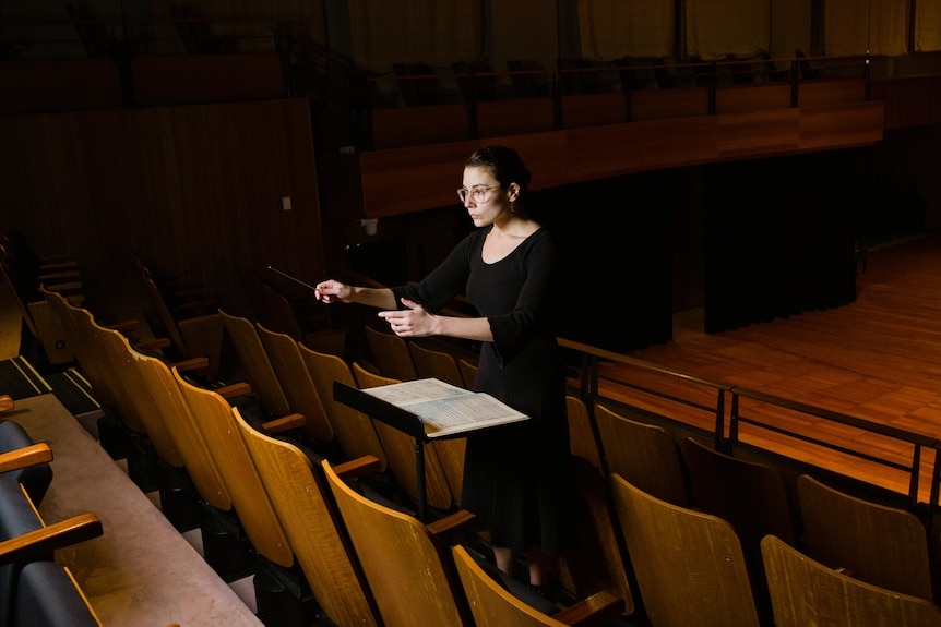 Wide shot of Nicky Gluch conducting with hands hovered over music sheet in concert hall.