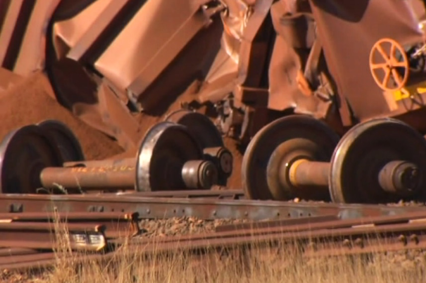 Axles from an iron ore train lie on the ground near other wreckage.