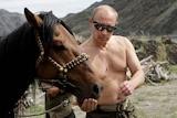 Russian Prime Minister Vladimir Putin feeds a horse