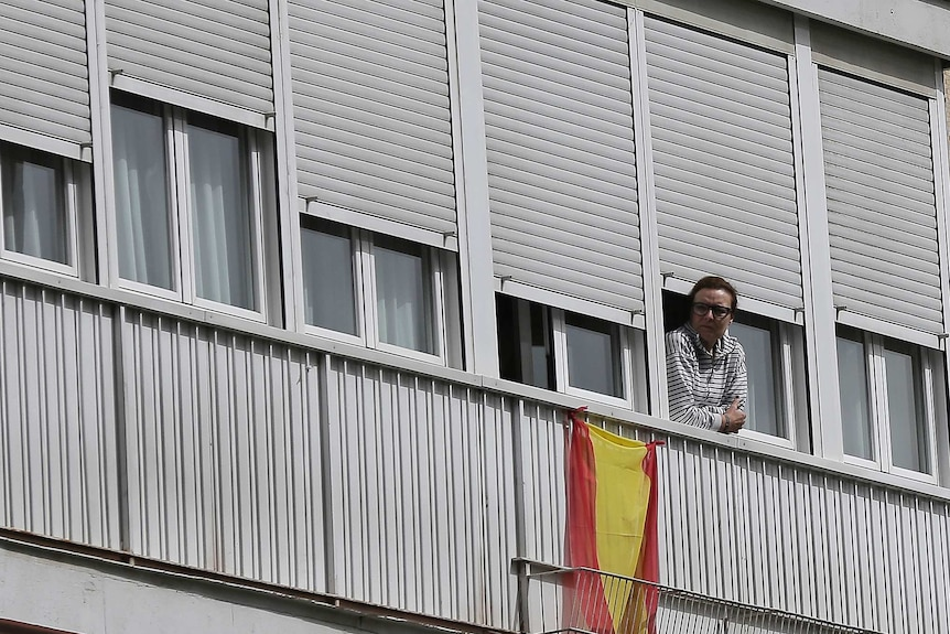 A woman looks out from a balcony next to a Spanish flag in Madrid, Spain.