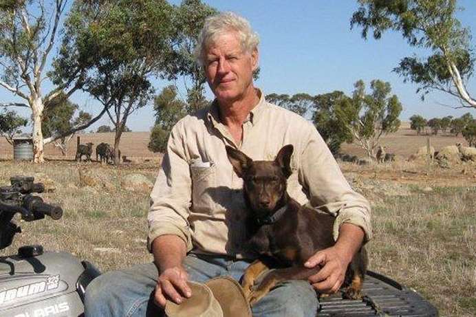 Picture of man sitting on quad bike with dog on his lap