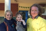 A blonde woman in dark blue jumper and scarf holding young boy standing next to curly haired male in yellow shirt