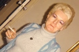 An angled shot of Shirley Finn standing indoors holding a cigarette and wearing a blue outfit and blue bag.