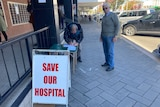 """Two elderly men stand on a main street sidewalk. A sign reading """"SAVE OUR HOSPITAL"""" is in the foreground"""