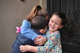 Three young children, two girls and a boy embrace outside a door.