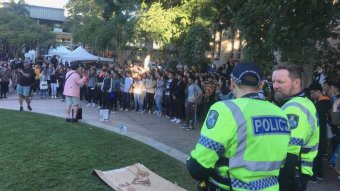 Police and Chinese students stand on the campus at the University of Queensland.