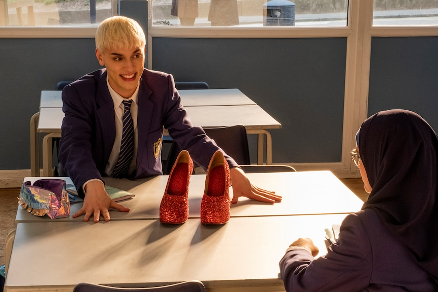 Max Harwood sits at a school desk, wearing a navy blazer and tie and, with hands outstretched, is beaming at glittery red heels.