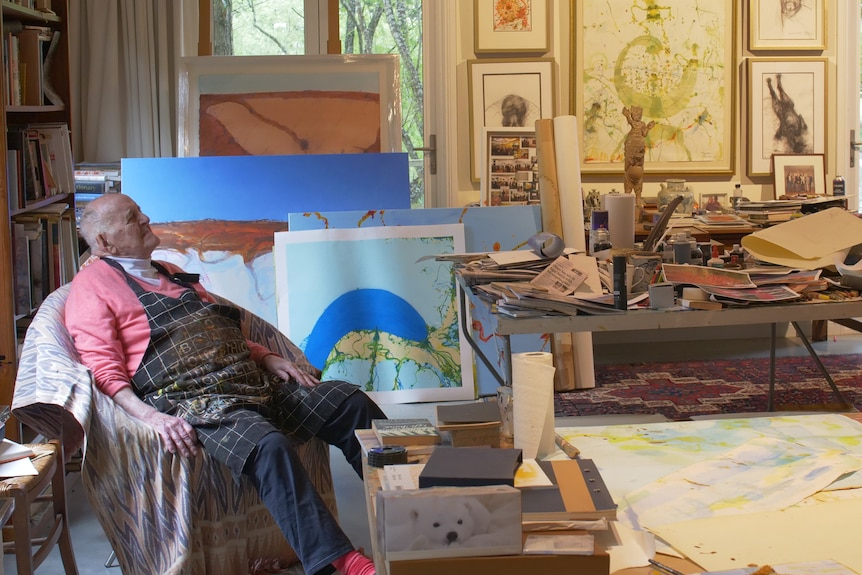 An elderly man in sweater and art smock sits in an art studio filled with canvases and tools
