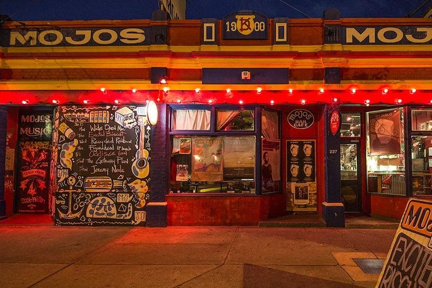 The exterior of Mojos bar in Fremantle at night with warm lighting and a dark sky.