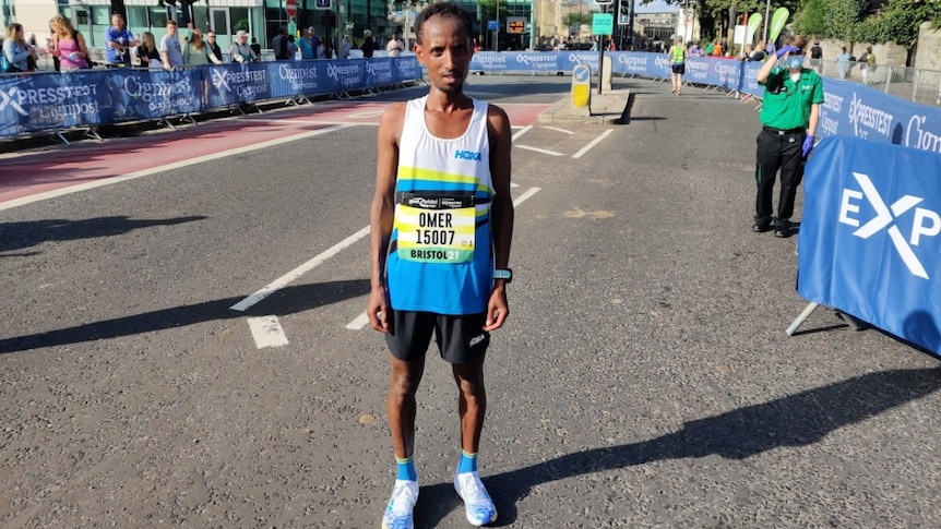 A man stands wearing a blue and white running singlet on an empty road