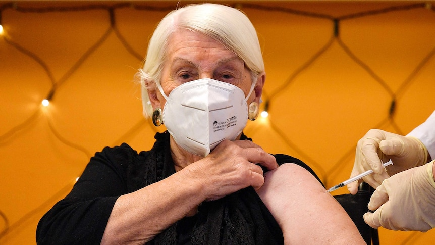 An elderly woman with white hair and wearing a mask pulls up her black shirt while someone administers a needle to her arm.