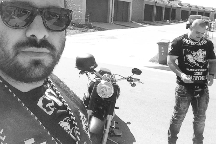 A black and white photo of two men wearing vests standing next to a motorcycle with a row of buildings in the background.