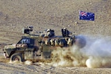 A Bushmaster Infantry Mobility Vehicle drives through a patch of bulldust in Afghanistan