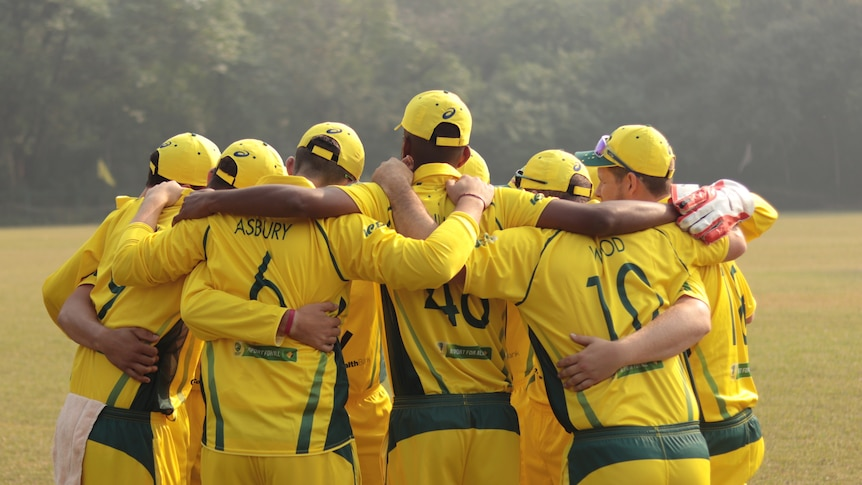 A group of men stand in a huddle wearing yellow cricket kit
