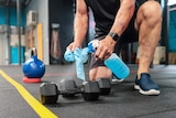 A man kneeling in a gym holds a bottle of disinfectant and sprays it on a dumbbell while he holds a rag in his other hand.