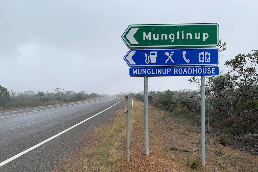 A large, green road sign shows the turn-off to Munglinup and the Munglinup Roadhouse