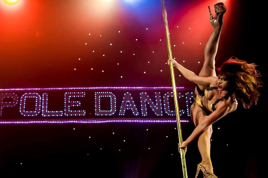 A girl in a bikini and sparkly platform heels winds around a pole on stage in front of a sign that says 'pole dance'.