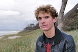 Curtis Cloake sits on the beach in Byron Bay