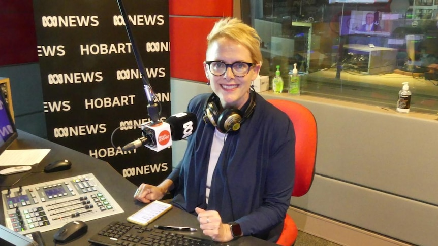 Woman wearing glasses and with headphones around neck in front of microphone in radio studio.