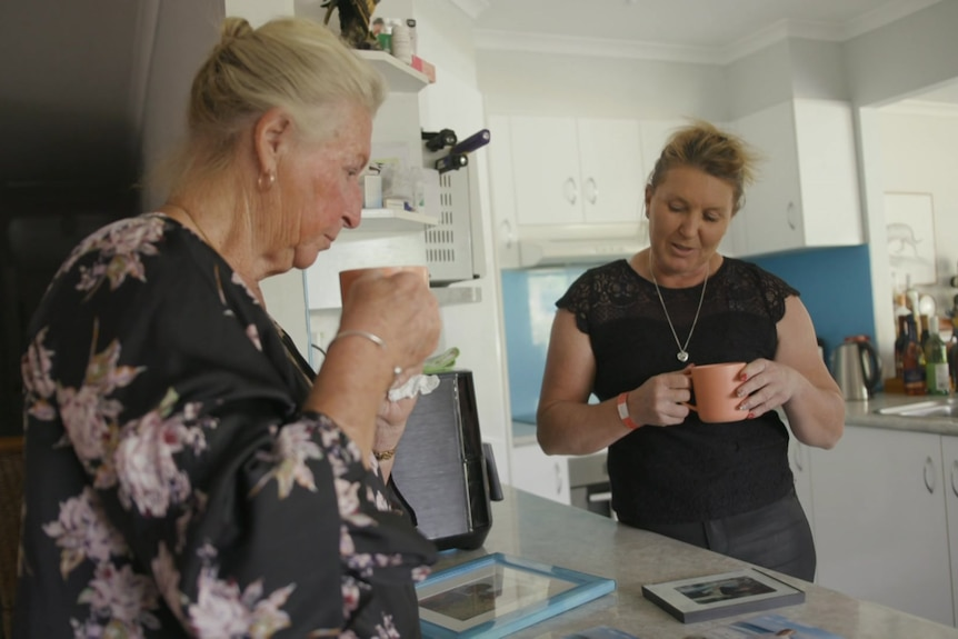 Women standing in a kitchen looking at pictures.
