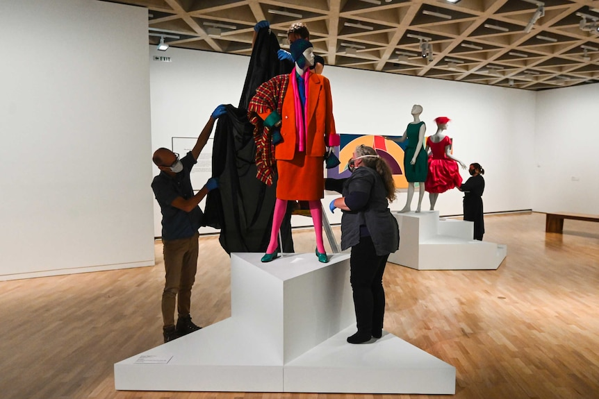 Art gallery staff wearing face masks and gloves tend to a piece of fashion art at the national gallery