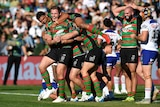A tall rugby player in red and green is hugged by his teammates after scoring a try on a grassy field.