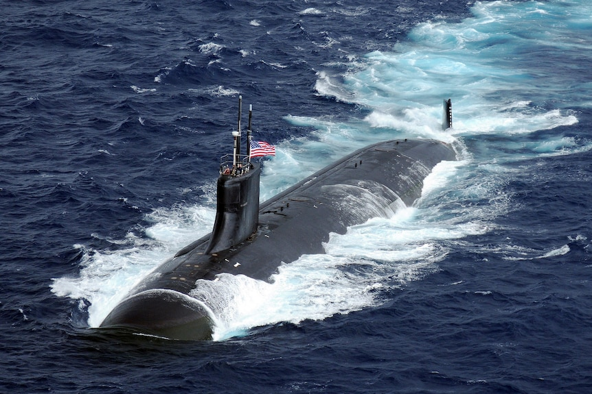 Submarine with Unites States flag is semi submerged in water