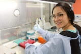A woman in glasses wearing a lab coat and smiling holds a syringe in a lab.