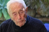 A very old man in a navy jumper sits at an outside table with glasses of wine in front of him.