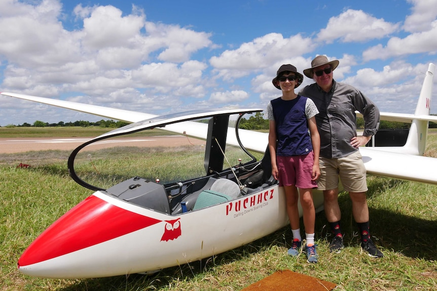 13 year old boy and man standing next to glider aircraft