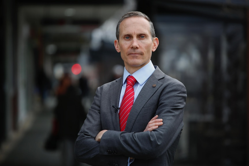 Andrew Leigh wearing a dark grey suit, blue shirt and red tie, standing with arms folded.