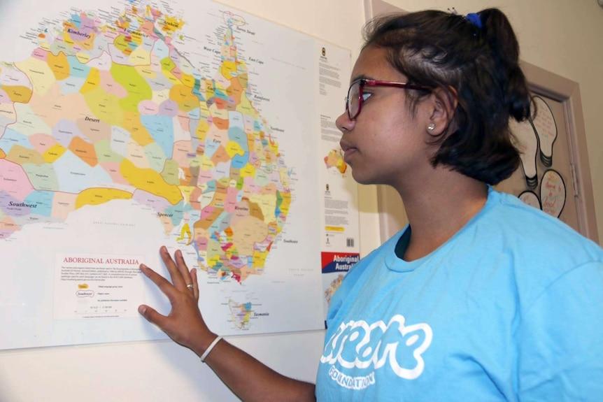 Shannieka Martino examines a map on Australia on a wall.