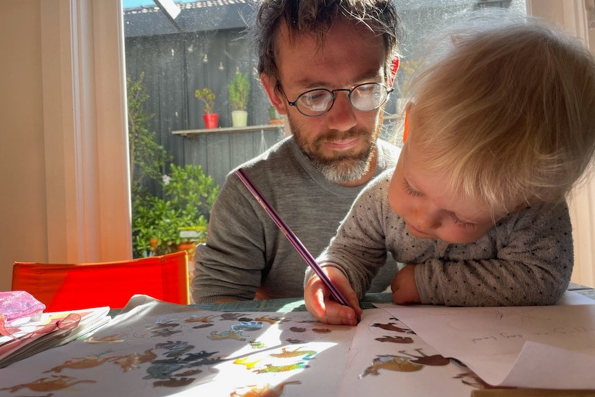 A man in glasses looks over the shoulder of a young girl who sits on his lap, drawing at the table.