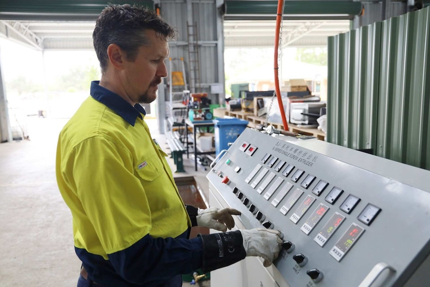 """A man in a high vis t-shirt stands next to a machine with buttons reading """"extruder"""""""