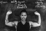 Cass Pickard stands in front of a blackboard displaying her personal bests - 150kg squat, 75kg bench, 192.5kg deadlift