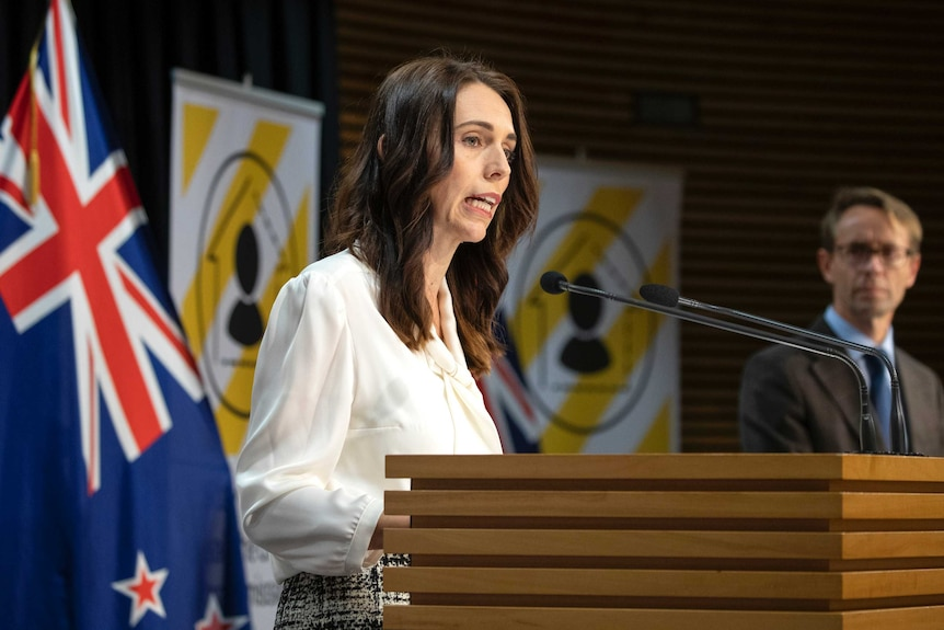 Jacinda Ardern stands at a lectern. Behind her is a New Zealand flag and two signs with yellow and white striped posters